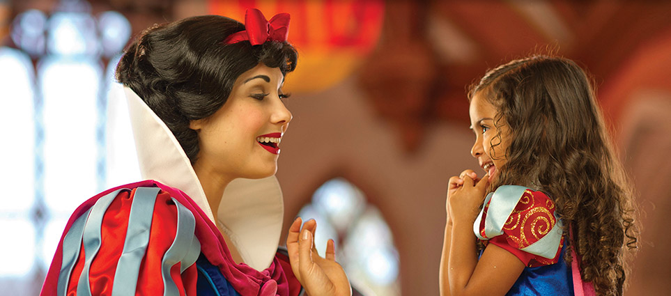 Snow White smiling at little girl dressed as Snow White
