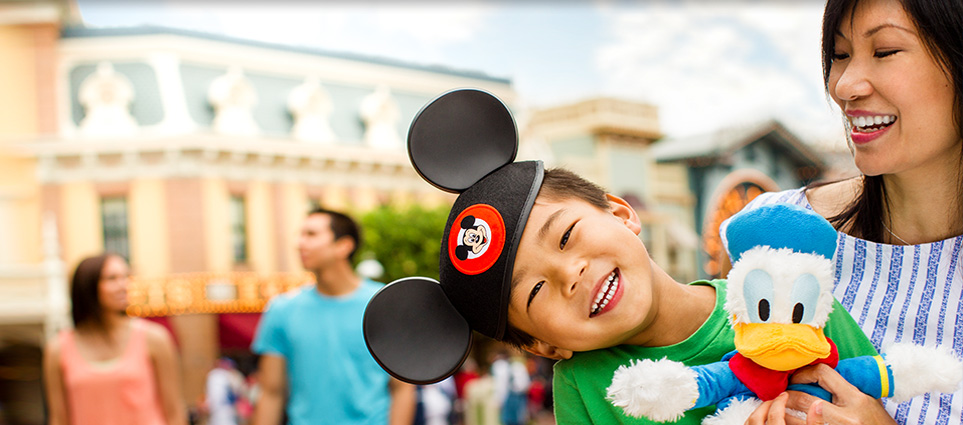 At Disneyland boy on vacation wears Mickey Mouse ears and plays with Donald Duck toy